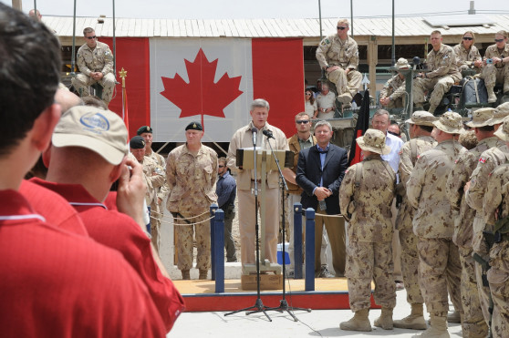 Prime Minister Stephen Harper acting like he actually cares about the military, with Chief of the Defence Staff General Walter Natynczyk to his right, as Harper addresses troops in Afghanistan.