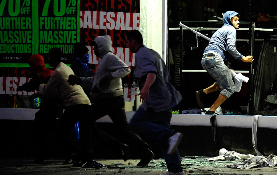 Looters run from a clothing store in Peckham, London August 8. Rioting and looting spread across London on Monday as hooded youths set buildings and cars ablaze, smashed shop windows and hurled bottles and stones at police in a third night of violence in Britain's worst unrest in decades. (Photo: REUTERS / Dylan Martinez )