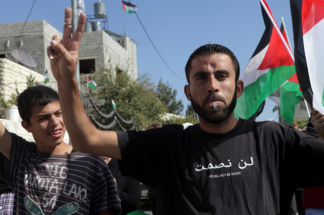 "A protester makes the ""V"" sign and wear a tshirt with the slogan ""we will not be silent"" during the weekly demonstration against the occupation and the settlement in the West Bank village of Nabi Saleh; on Friday 28.10.2011."